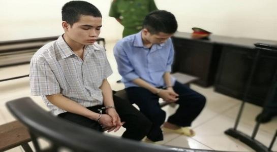 Hai bị cáo trước vành móng ngựa trong phiên tòa sơ thẩm.