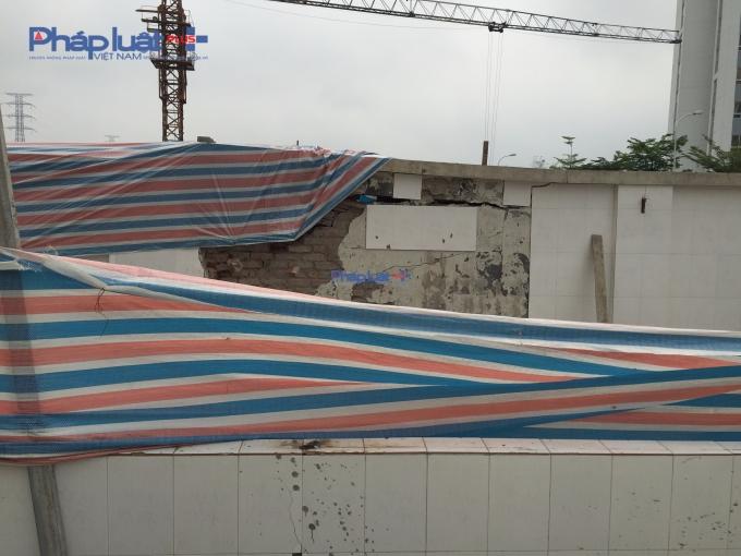 Tường rào bênh viện tiếp giáp với công trình xây dựng vị hư hỏng nặng. (Ảnh Thanh Thắng)