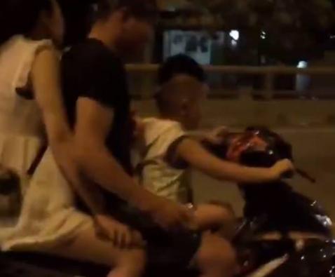 Bé trai điều khiển xe máy đi trên đoạn đường tối. (Ảnh cắt từ clip).