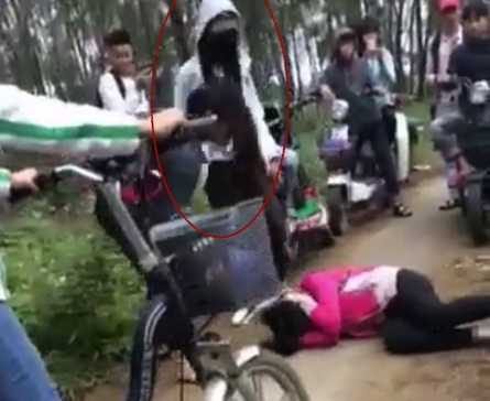 Hình ảnh nữ sinh H bị các bạn cùng lớp đánh gục ở bãi phi lao (ảnh cắt từ clip).