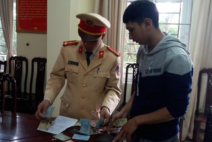 Thượng úy CSGT kiểm tra lại toàn bộ tài sản trong ví để trao trả lại cho anh Hoàng.