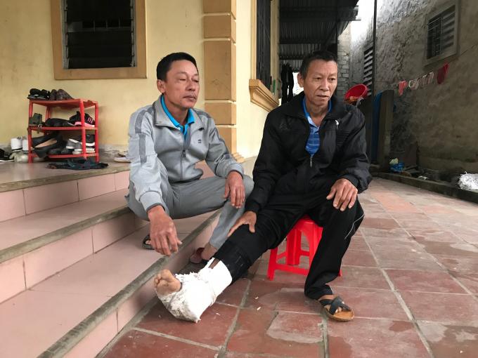 Ông Nguyễn Văn Năng (áo đen) người bị chính con ruột đánh đập đến gãy xương sườn, bầm tím khắp người.