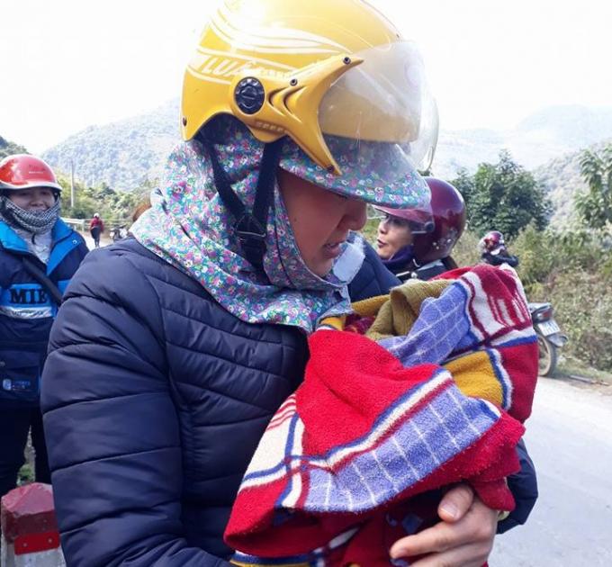 Đứa trẻ được các cô giáo bế trong vòng tay ấm áp.