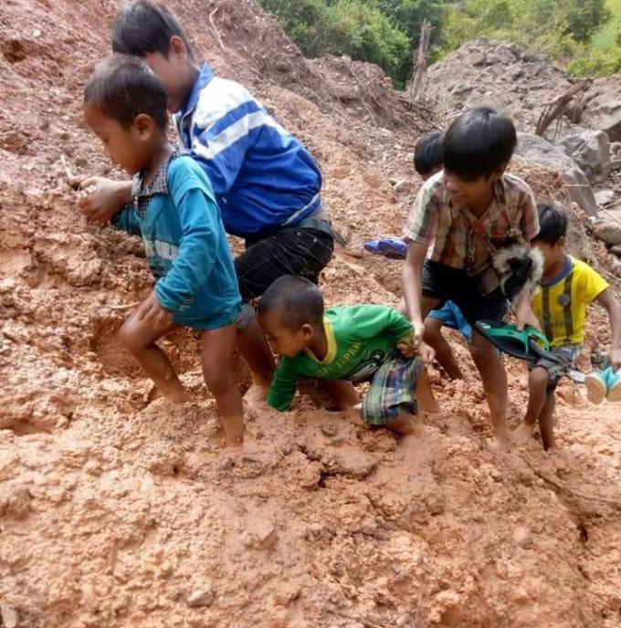 Học sinh phải lội bùn ngập đến đầu gối để tới trường học chữ.