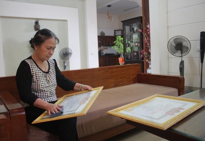 Bà Nguyễn Thị Huệ lau thật sạch tấm bằng Tổ quốc ghi công của người chú và em chồng trước ngày giỗ.