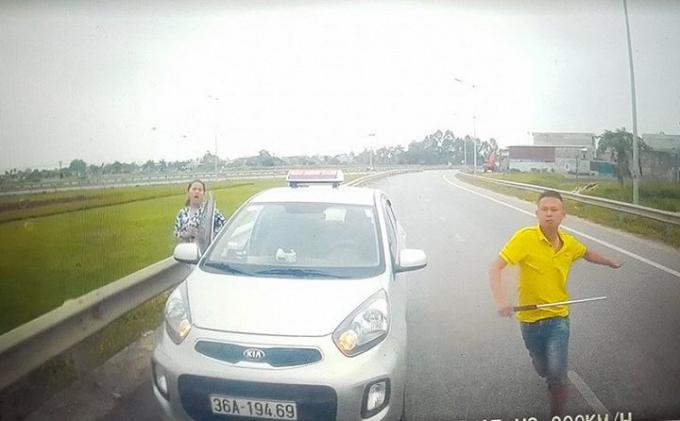 Không được nhường đường, thanh niên này còn mở cửa xe và rút tuýp sắt đòi xử tài xế. (Ảnh: cắt từ clip)