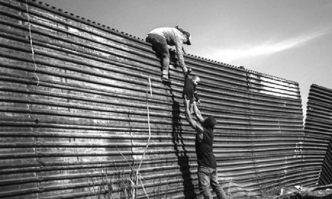 Một gia đình nhập cư trèo qua hàng rào ở biên giới Mỹ - Mexico hồi cuối tháng 11 năm ngoái.