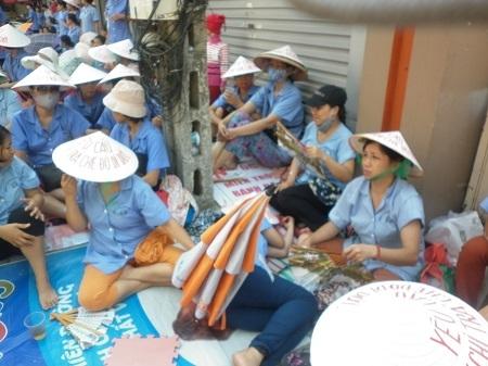 Những người công nhân tại Công ty Dệt nằm vạ vật trên vỉa hè đòi tiền hỗ trợ. Ảnh: Như Trường