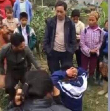 """Nam thanh niên mặc đồng phục học sinh """"cướp vợ"""" phải quỳ xuống nhấc tay lên đầu để xin lỗi người đàn ôn người Mông do bắt nhầm vự của anh ta. Ảnh cắt từ clip."""