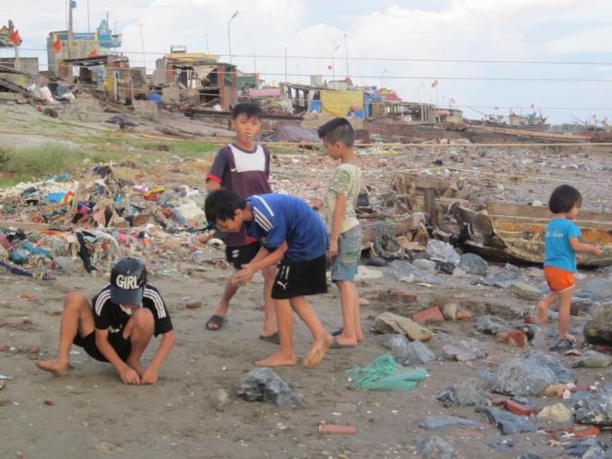Nơi vui chơi của trẻ em cũng ngay trên bãi rác. Trên bờ là hoạt động buôn bán, trò chuyện hàng ngày.