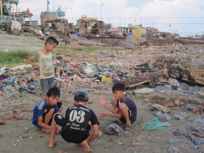 Trẻ em vui chơi bên những đống rác ven biển.