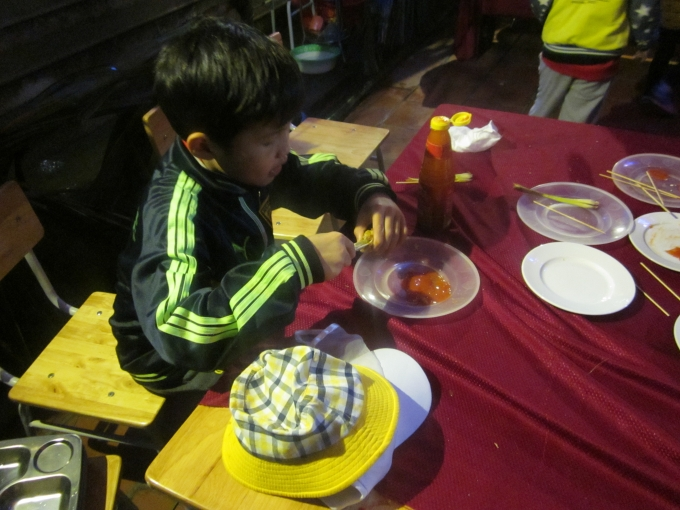 Cậu bé ngồi ăn rất ngon lành...