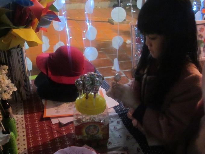 Cô bé đang trang trí cho cửa hàng nhỏ của mình bằng những cây kẹo ngọt.