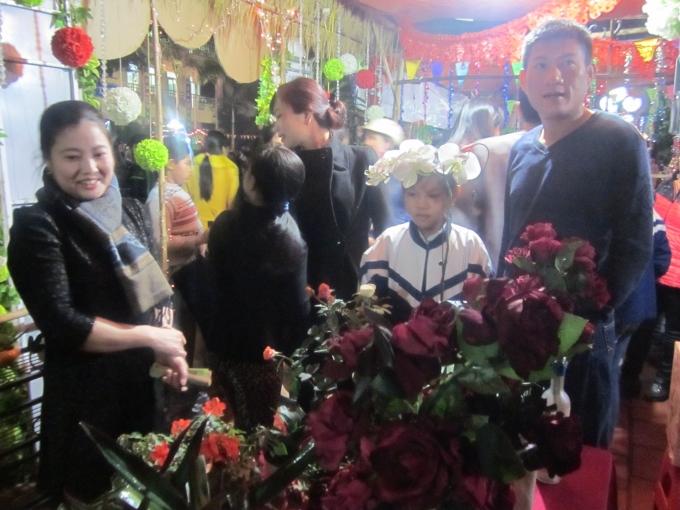 Một em học sinh đang giới thiệu và bán hoa trong trại