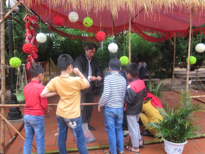 Thầy hiệu trưởng đang hướng dẫn học trò của mình trang trí lều trại.
