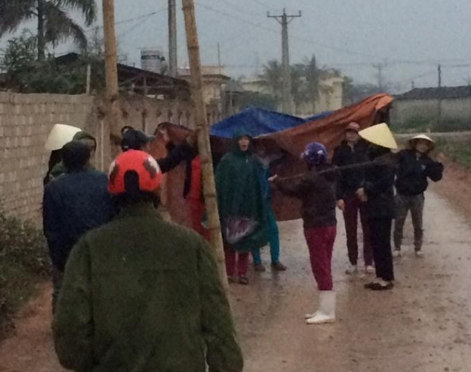 Bất chấp mưa gió... khá đông người dân đứng phản đối.