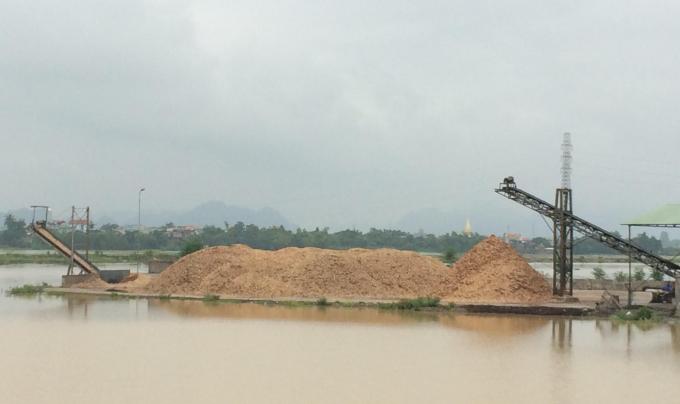 Bãi tập kết dăm gỗ lấn chiếm ra sông Hoàng Long gây ảnh hưởng đến dòng chảy. Ảnh: Nguyệt Chi