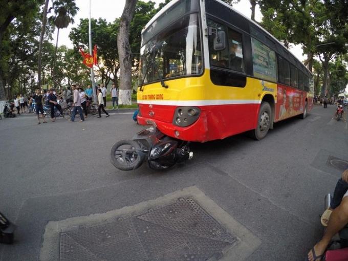 Xe máy chui vào gầm xe buýt.