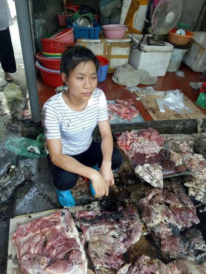 Hình ảnh chị Xuyên thất thần bên đống thịt lợn bị đổ chất thải. Ảnh: Facebook.