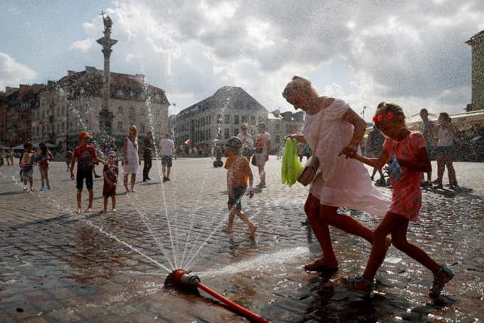 Không ngại ướt, người dân chơi đùa với vòi nước từ xe cứu hỏa khi nhiệt độ vượt mức 37 độ C tại Prague, Cộng hòa Séc. Ảnh: David W Cerny/Reuters