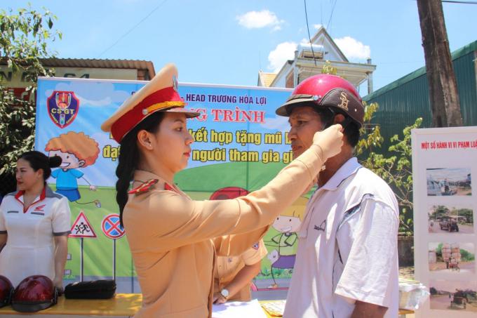 CSGT Đắk Lắk hướng dẫn người dân đội mũ bảo hiểm và cài quai đúng cách khi tham gia giao thông.(Ảnh:Đình Thảo)