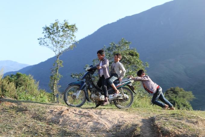 Những đứa trẻ đang tập đi xe máy của gia đình.