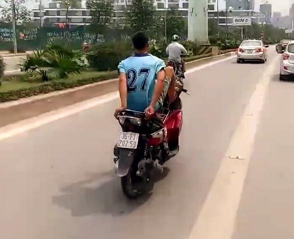 Nam thanh niên điều khiển xe máy bằng 2 chân không đội mũ bảo hiểm đi vào làn đường dành riêng cho BRT.