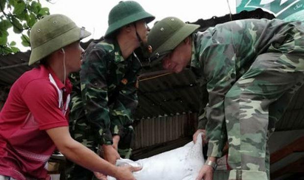 Cán bộ Đồn Biên phòng cảng Cửa Lò - Bến Thủy giúp dân chằng chống nhà cửa.