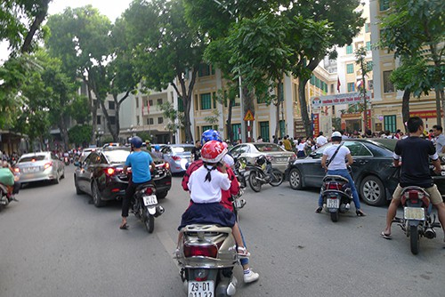 Đối diện trường Tiểu học Trần Quốc Toản, xe của phụ huynh học sinh đón con đỗ kín lòng đường. Hầu hết học sinh vẫn được cha mẹ đưa đón bằng xe máy, ô tô…