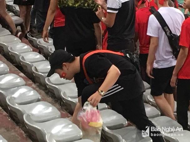 Cổ động viên Việt Nam nán lại dọn rác trên sân vận động. Ảnh: Lang Quốc Khánh