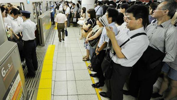 Người dân đứng xếp hàng tại một ga tàu điện ngầm ở Tokyo, Nhật Bản.