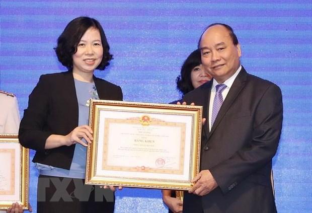 Thủ tướng Nguyễn Xuân Phúc trao tặng Bằng khen của Thủ tướng Chính phủ cho Thông tấn xã Việt Nam vì thành tích xuất sắc tại WEF ASEAN 2018. (Ảnh: Thống Nhất/TTXVN)