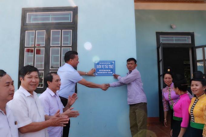 Ông Vũ Đình Tiến- Trưởng Văn phòng đại diện báo Pháp Luật Việt Nam khu vực phía Bắc (trong cùng bên trái) trao biển bàn giao Nhà văn hóa cho đại diện xã Nà Nhạn (huyện Điện Biên).