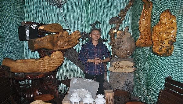 Nghệ nhân Trần Đức Vinh bên các tác phẩm gỗ lũa nghệ thuật của mình