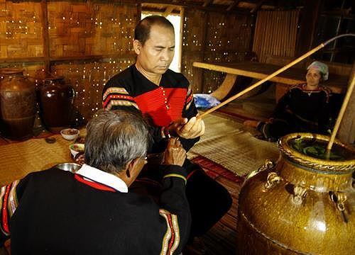 Thầy cúng cầm vòng đồng đeo trên tay gia chủ và đọc lời khấn cầu sức khỏe, nhắc lại lời hẹn ước
