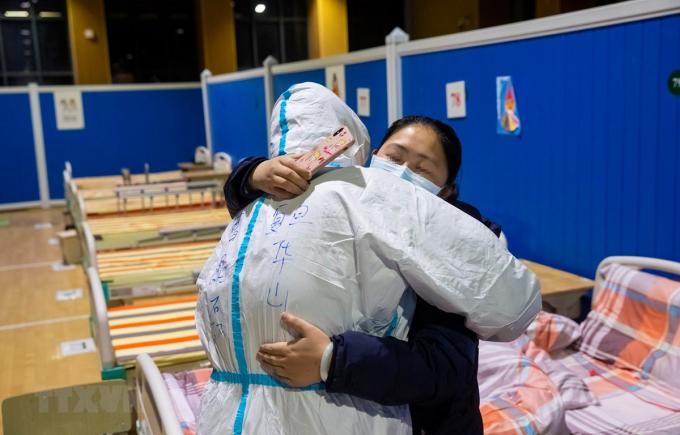 Bệnh nhân nhiễm COVID-19 tạm biệt bác sĩ sau khi được chữa khỏi tại bệnh viện ở Vũ Hán, tỉnh Hồ Bắc, Trung Quốc, ngày 9/3/2020. (Ảnh: THX/TTXVN)