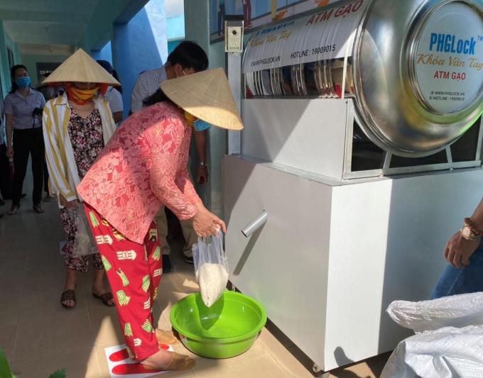 Người dân trực tiếp nhận gạo từ máy ATM gạo.