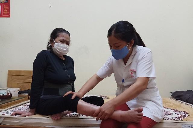 Chị Nguyễn Thị Thiêm - Nhân viên y tế Trung tâm Nuôi dưỡng và điều dưỡng người có công số 2 đang xoa bóp cho bà Vương Thị Là - cựu thanh niên xuong phong. Ảnh: Trần Oanh