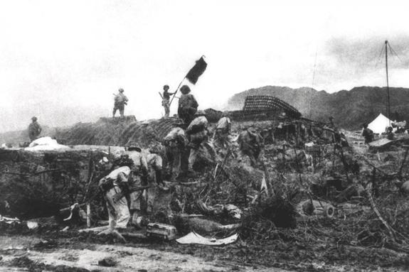 Bộ đội Việt Nam vẫy cờ trên nóc một hầm chỉ huy của quân Pháp tại Điện Biên Phủ, ngày 7-5-1954. Ảnh: AFP.