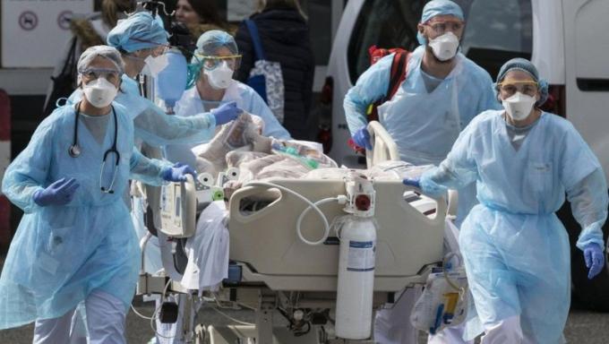 Nhân viên y tế ở Pháp chuyển một bệnh nhân đến bệnh viện. Ảnh: AFP