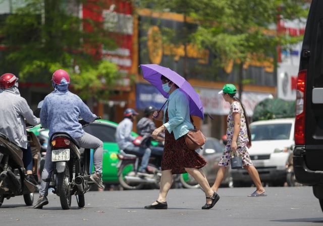 Hai người phụ nữ vội vã sang đường ở phố Xã Đàn.
