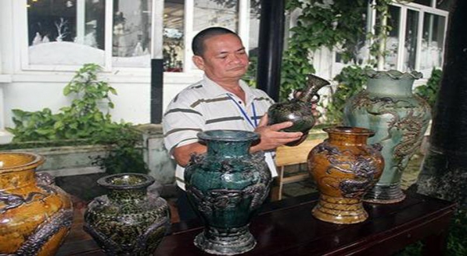 Nghệ nhân Đặng Văn Trịnh bên những sản phẩm gốm Mỹ Thiện.