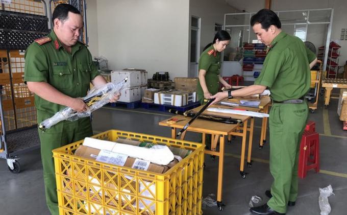 Lực lượng chức năng tháo kiểm tra các gói bưu phẩm chứa vũ khí, công cụ hỗ trợ.