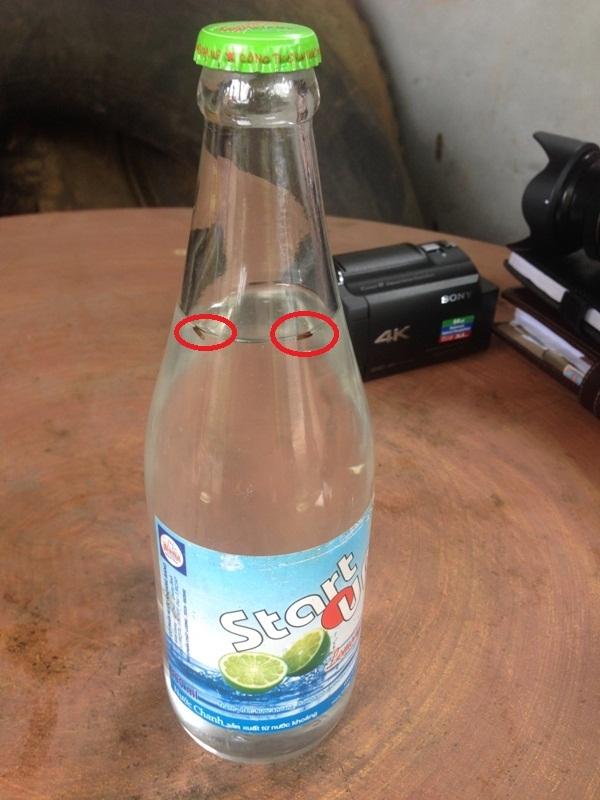 Hai vật thể lạ có maù đen sẩm nổi lềnh bềnh trong chai nước ngọt có nhẫn hiệu Start Up. (Ảnh: Văn Ba)