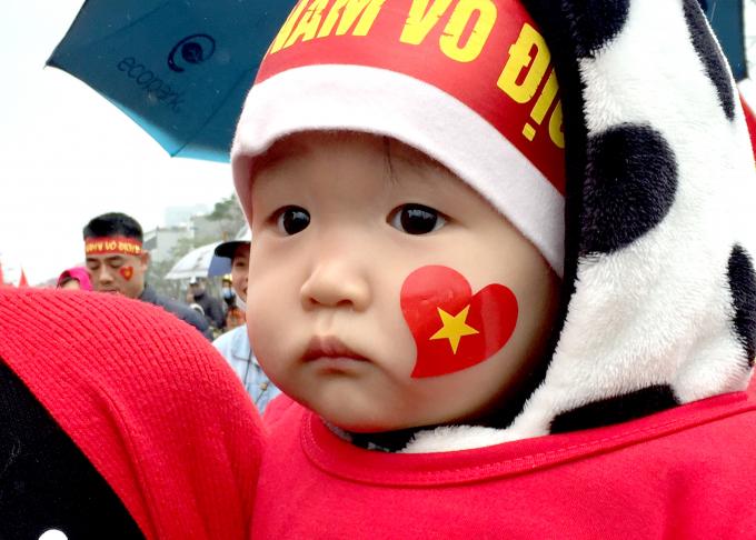 Một đứa trẻ dường như cũng đang ngóng chờ được chứng kiến hình ảnh của các tuyển thủ U23 Việt Nam.