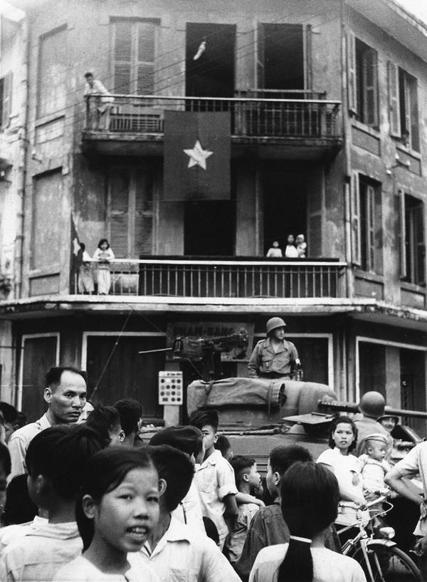Lá cờ đỏ sao vàng bay phấp phới trên một nhà dân Thủ đô, ngay dưới đó là một xe lính Pháp chuẩn bị rút khỏi Hà Nội.