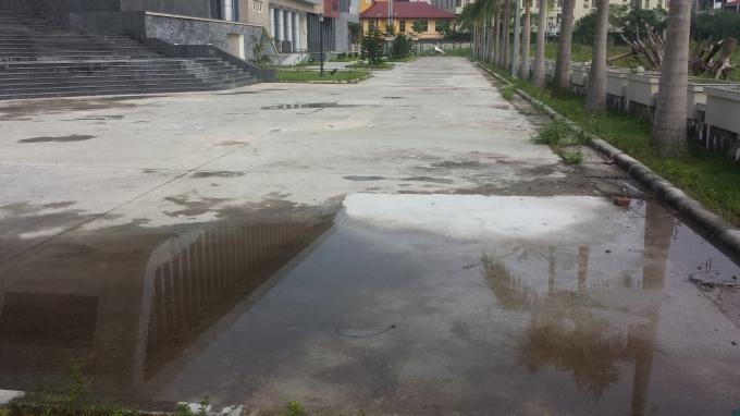 Bãi nước đọng trên mặt sân soi bóng công trình.