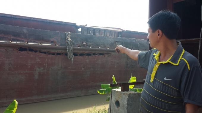 Ông Vũ Văn Hùng, Giám đốc Công ty TNHH Trung Hiếu chỉ về phía con tàu hư hỏng nặng.