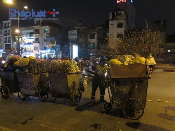 Các xe rác của công nhân môi trường vốn đã đầy ăm ắp nay lại phải làm thêm nhiệm vụ chuyên chở cây đào, quất bỏ đi.