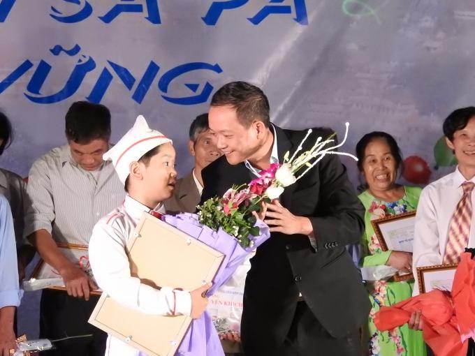 Ông Vũ Hùng Dũng - Chủ tịch UBND huyện Sa Pa lên trao quà và hoa cho Trường Tiểu học thị trấn Sa Pa đạt giải đặc biệt.